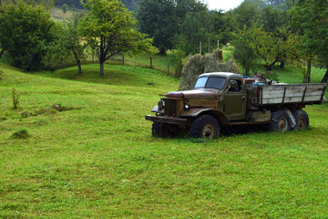 Very old gray truck without trademark on the green grass