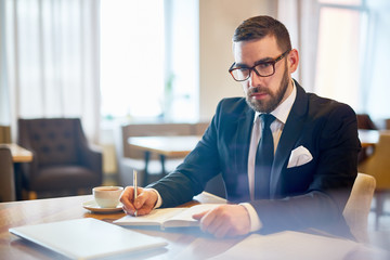 Waist-up portrait of confident bearded entrepreneur in classical suit posing for photography while working at spacious cafe