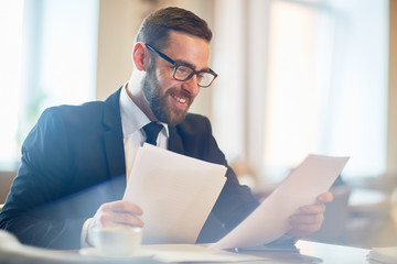 Cheerful young manager in eyeglasses analyzing results of accomplished work while sitting at office desk, blurred background