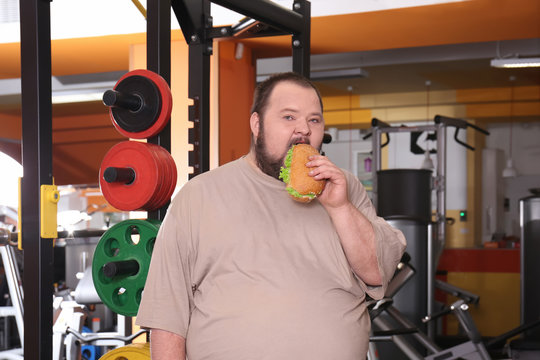 Overweight man eating sandwich in gym