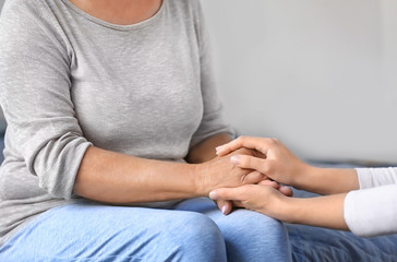 Mature and young women holding hands indoors. Elderly care concept