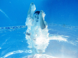 Rotated photo of man jumping into a pool