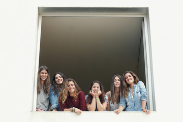 Group of six girls looking from up on a window