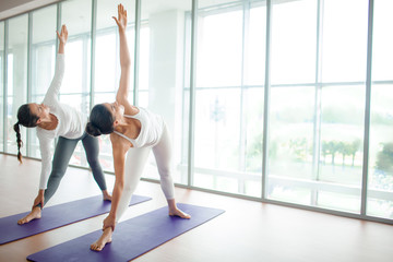Active females keeping their stretched arms raised during exercising in gym