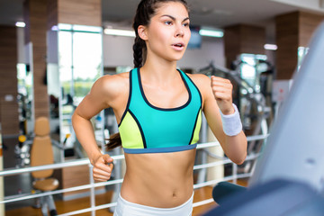Modern girl running on treadmill during workout in gym