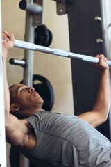 Young Man Exercising in Gym with Bench Press