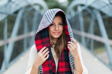 Beautiful woman with a scarf wrapped around her head standing on a bridge