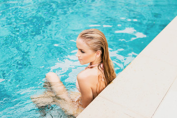 Blonde girl relaxing by the pool