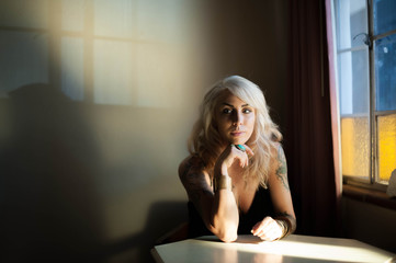 Alternative Style Blond Woman Sitting at Table By Window