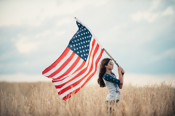 A young woman waving American flag while standing in a field Fotoväggar
