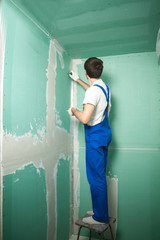 Portrait of young pretty man on construction site: male worker plastering walls with spatula while remodeling office