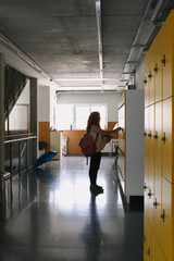 Girl in a school corridor opening a locker