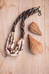 Tribal african bone beads with decor nature element on wooden background.