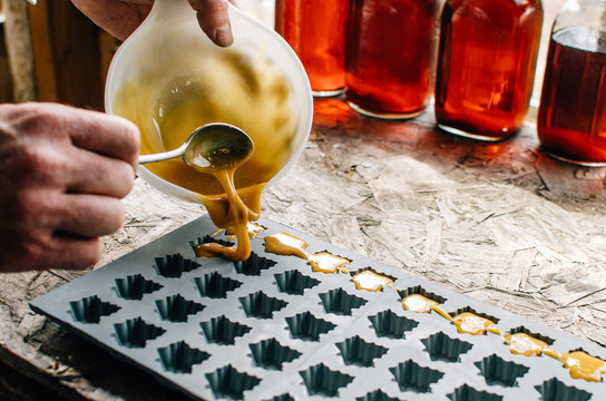 pouring maple sugar into mold for candy