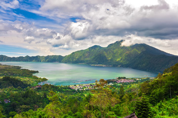 Panoramic view of a lake surrounded by mountain, tropical landscape with colorful clouds in the sky. Fisheries and settlements on the shore. Danau Batur, Gunung Batur, Kintamani, Bali, Indonesia.
