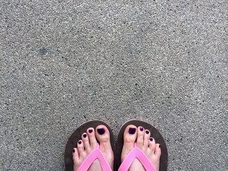 Sandal, Close Up on Girl's Violet Nail and Feet Wearing Pink Sandals on Cement Floor Background Great For Any Use.