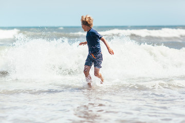 child running from a breaking ocean wave