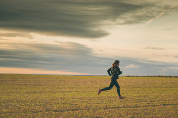 young woman running in the fields at sunset