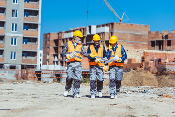 Three workers in hardhats at construction site