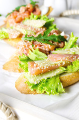 Sandwich with salmon served with fresh salad and sesame