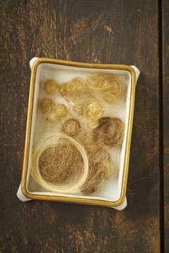 Curls and strains of childrens' hair in a vintage porcelain box
