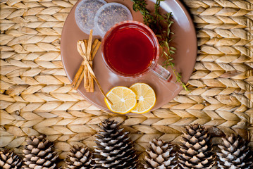 Herbal tea with cinnamon and lemon on a wicker basket. Christmas cones