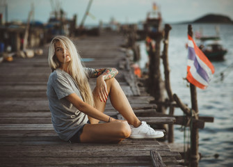 Hipster girl sitting on wooden pier in the rays of the setting sun. A vacation in Thailand. Hands with tattoos