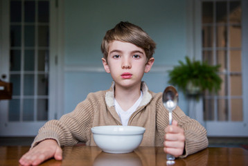 Boy sits at the dinner table with a bowl and spoon