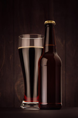 Brown beer longneck bottle and glass weizen with porter on dark wood board, vertical, mock up. Template for advertising, design, branding identity.