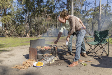 Grey nomad couple tending meat, vegetables and fruit cooking on grill at campfire