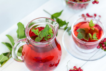 Redcurrant drink in transparent glass carafe and cup. Clear glass vase with red currant berries on the white wooden background