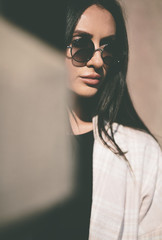 portrait of trendy woman with round sunglasses in closeup