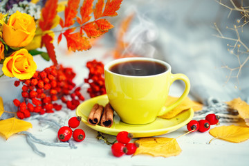 Cup of coffee, autumn leaves and flowers on a wooden table. Autumn still life. Selective focus.