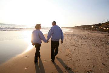 Elderly couple holding hands and walking on the beach