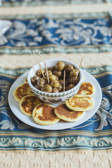 Russian aperitif: green olives and homemade blinis