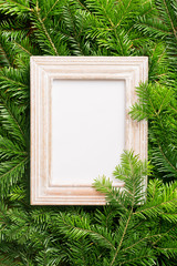 Christmas copy space. Picture frame on a green Christmas tree background. Copy space. Blank wooden photo frame on Christmas tree branches.