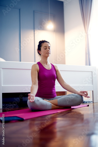 40 Year Old Charming Woman Doing Yoga Meditation At Home In Front Of The Bed