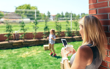 Mother watching mobile while her son plays in the garden
