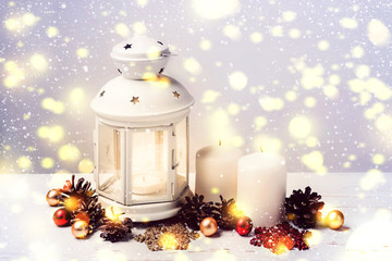 Burning Candle Lantern and Christmas composition of fir cones an