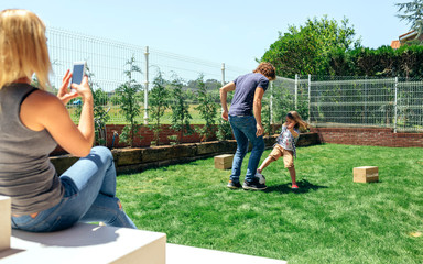 Mother taking mobile photo of her husband and son playing in the garden