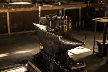 A metal anvil sits in a blacksmith workshop with a hammer on top