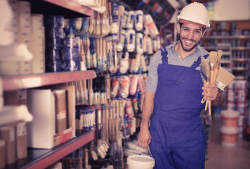 Positive builder with paint and brushes in paint shop