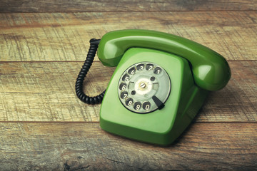 Old green telephone on a wooden background