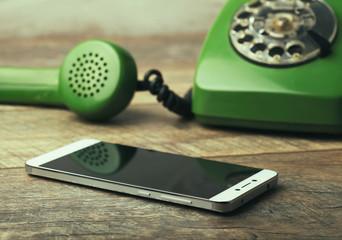 Old green vintage telephone vs modern mobile phone show evolution in telecommunications.