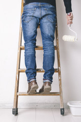 Man painting a wall on a wood ladder.