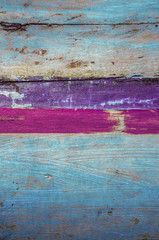 Old wooden boat detail; blue fishing boat with purple and pink stripes
