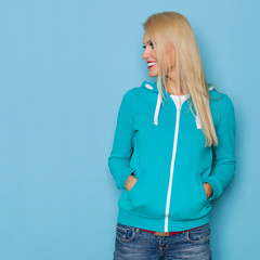 Smiling Blond Woman In Turquoise Sweater Is Looking Away