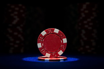 Closeup of poker chip on blue felt card table surface with spot light on chip