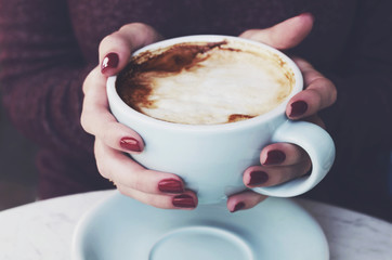 Cup of morning coffee with milk foam in woman's hands