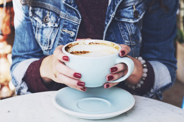 Woman in jeans jacket holding cup of cappuccino in her hands with red nails